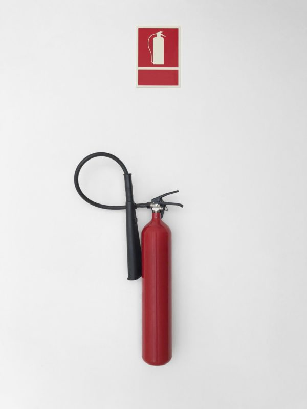 Fire extinguisher with sign alarm on a white wall. Warning